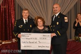 The $75,000 check presented to the Fire Chief and President from the Ladies Auxiliary President