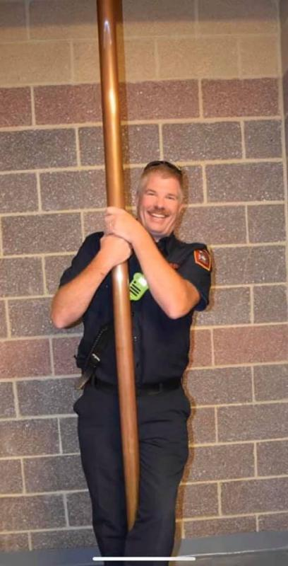 Chief Doug Insley taking a last ride down the Traditional Brass Fire Pole with the Officers and Members of HVFD present.