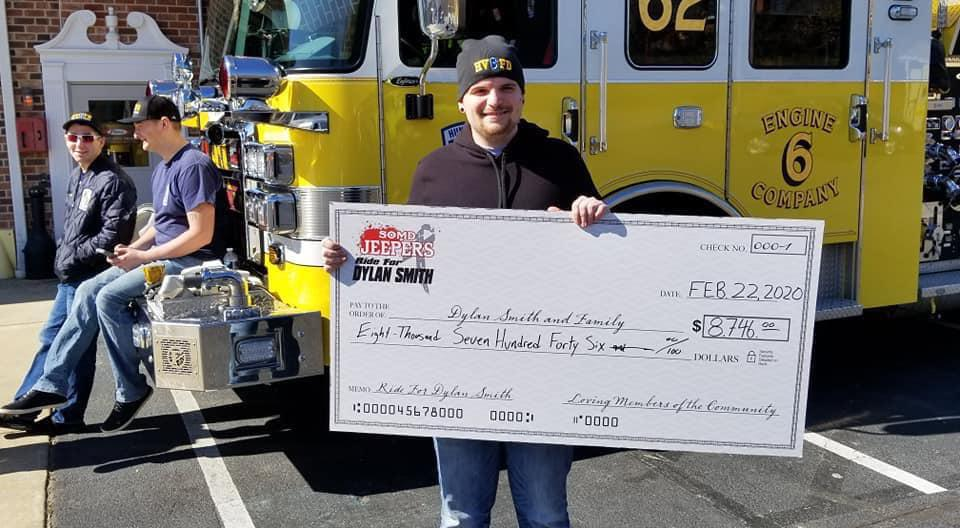 Ryan Smith receiving a donation from SO. MD Jeepers and the Supporting Community