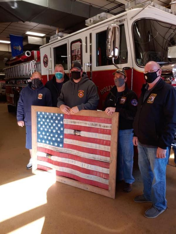 Chuck Latham presenting the Officers and Members with an American Flag made out of old fire hose from our department.